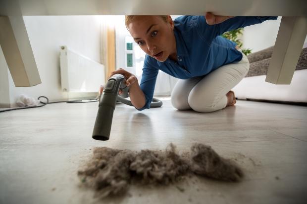 Frau reinigt Staub unter einem Tisch