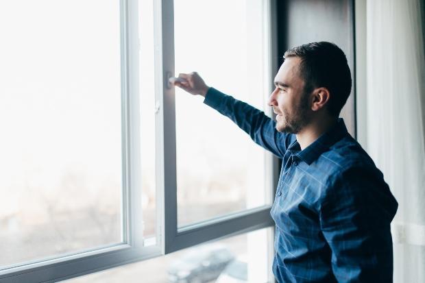 Mann öffnet Fenster - dies hilft bei viel Staub
