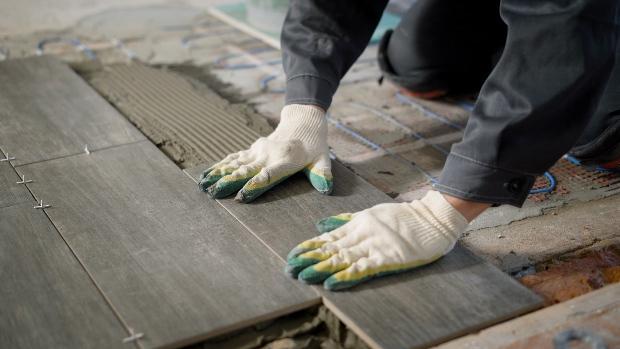 Mann verlegt Fliesen über eine Fußbodenheizung