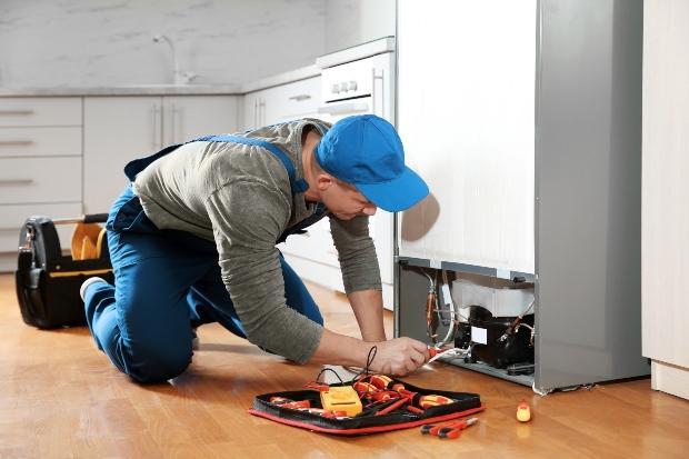 Mann repariert Kühlschrank - Prinzipumkehrung im Vergleich zur Luftwärmepumpe