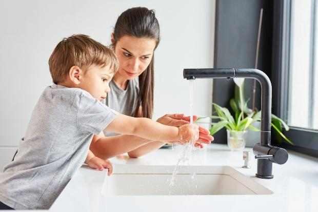 Mutter mit Kind am Wasserhahn in der Küche
