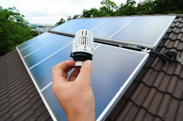 Heizungsthermostat symbolisch mit Solaranlage verbunden - Solarthermieheizung