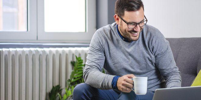 Junger Mann sitzt vor Heizung - Wärmeeffizienz steigern