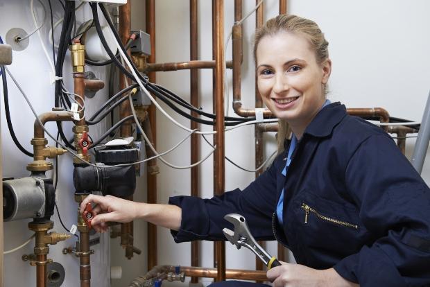 Handwerkerin repariert Heizungssystem