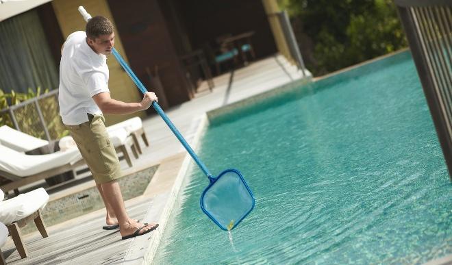 Jemand benutzt einen Kescher, um den Pool zu reinigen