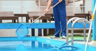 Mann bei der Poolreinigung mit einem Kescher