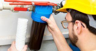 Handwerker montiert Aktivkohlefilter für die Wasserversorgung