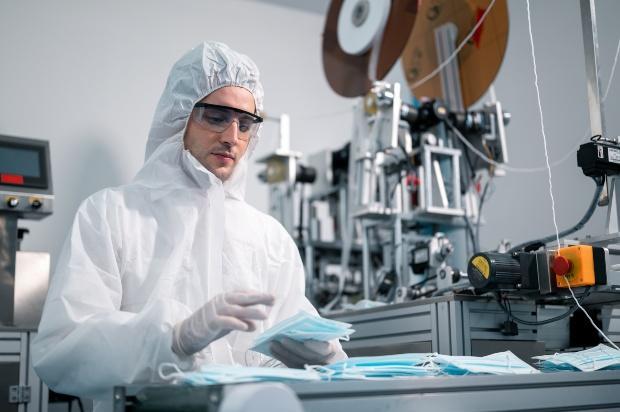 Junger Mann im Labor in einem Schutzanzug