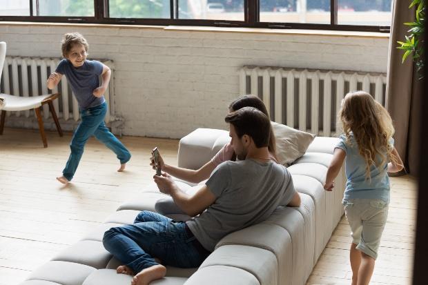 Junge Familie mit zwei Kindern im Wohnzimmer