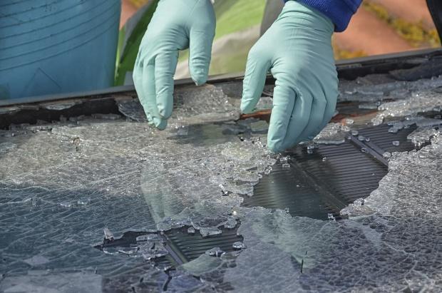 Jemand sammelt Glas eines zerstörten Solarpanels auf - Photovoltaik: Entsorgung