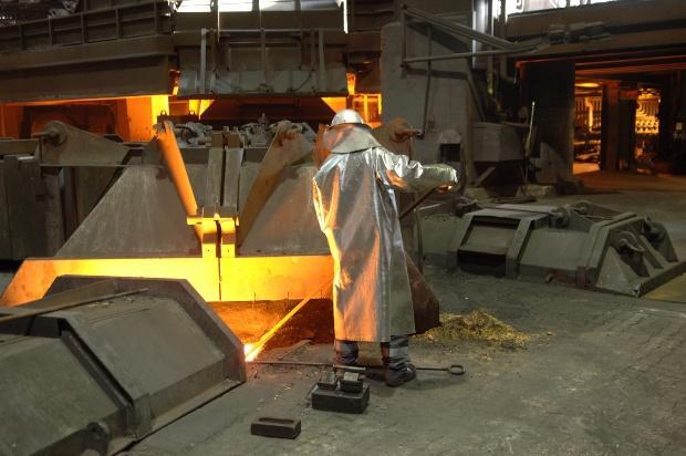 Mann arbeitet an einem Hochofen - spezielle Schutzanzüge bei hohen Temperaturen