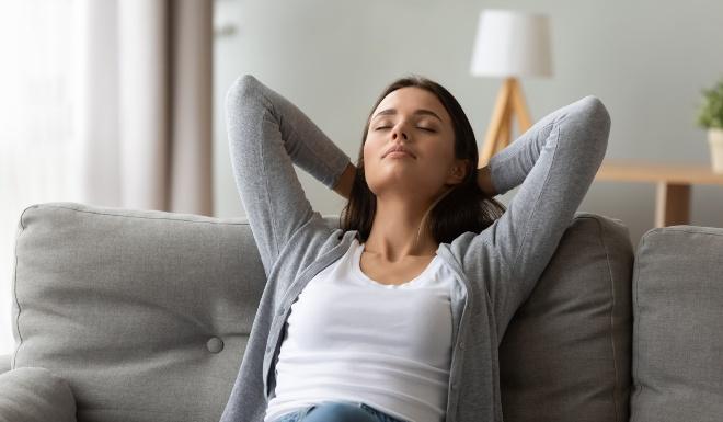 Junge Frau sitzt zuhause entspannt auf der Couch