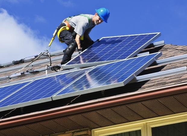 Ein Handwerker installiert ein Solarmodul auf einem Hausdach